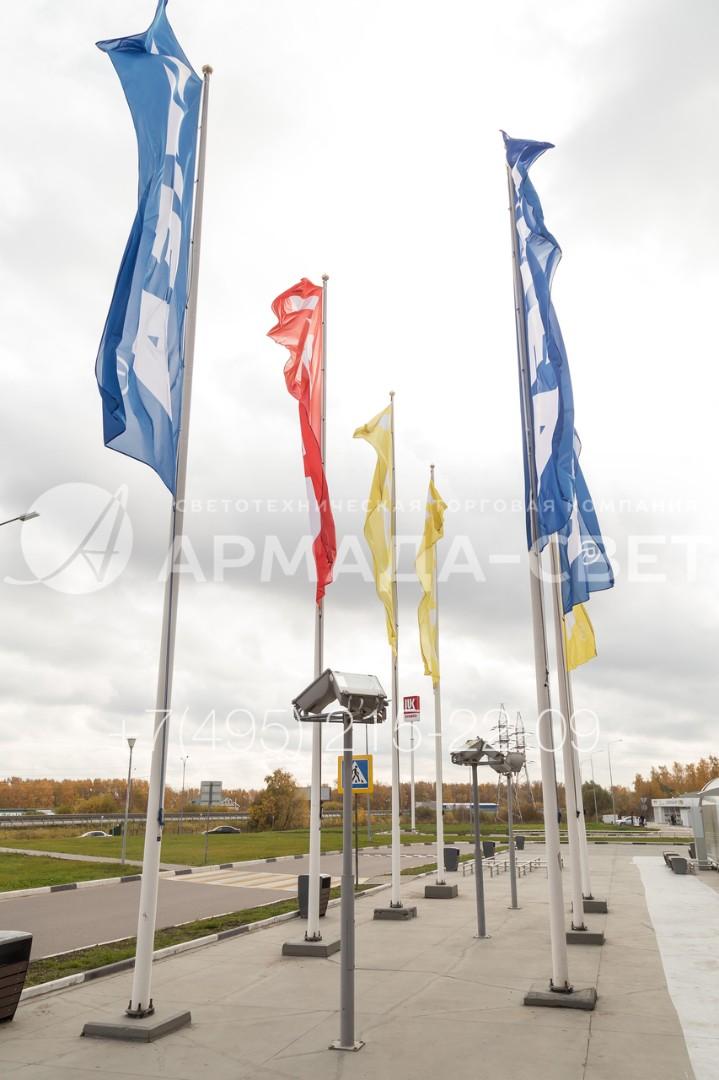 На фото приведен пример использования большого количества баннеров с названием торговой марки для привлечения клиентов к торговому центру. Использование моделей флагштоков из углеродистого проката позволяет сэкономить на строительстве.