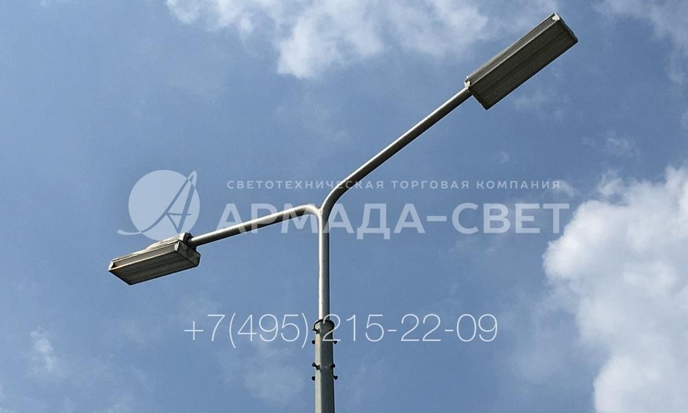 Кронштейн под консольные светильники с двумя рожками сделан из трубного проката с малым диаметром. На концах кронштейна закреплены светодиодные приборы освещения. Благодаря полым трубам провода для питания светильников проложены внутри конструкции. За счет этого верхняя часть опоры имеет красивый внешний вид.