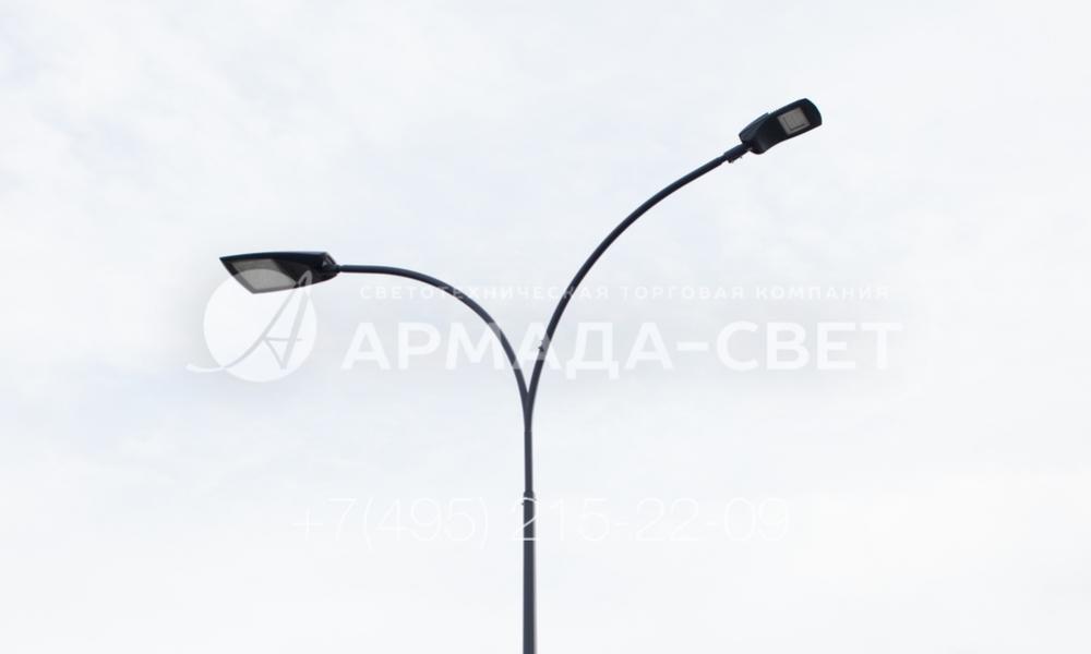 Пример консольного светильника с двумя рожками. При использовании такой модели световые приборы располагаются на рожках под углом в 180 градусов друг от друга и освещают пространство по обе стороны от стальной опоры. За счет этого можно осветить большую площадку или две противоположные стороны движения по автомобильной дороге.