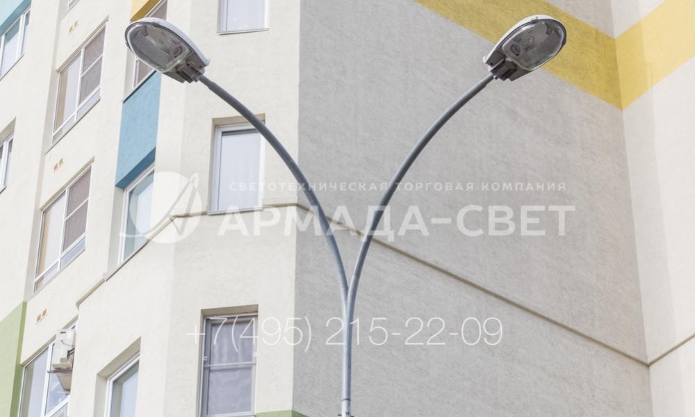 Если необходимо осветить поворот дорожки или проезжей части, часто используют кронштейны с двумя рожками, которые размещены под углом от 45 до 90 градусов друг от друга. На приведенном на фотографии варианте установлены светильники с газоразрядными лампами. Так можно увеличить безопасность передвижения людей и транспорта по улицам города.