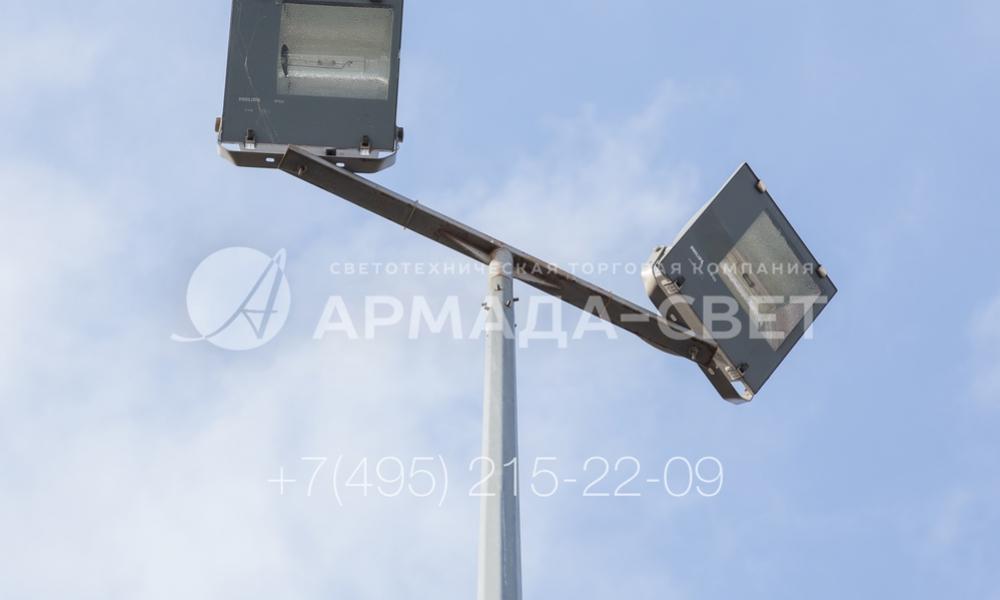 На фото изображен Т-образный кронштейн с прожекторами уличного освещения Этот кронштейн позволяет установить прожекторы на любую опору уличного освещения. За счет монтажных скоб, которые установлены на корпус прожектора, можно повернуть его и наклонить под нужным углом для точного направления луча света в нужную точку площадки.