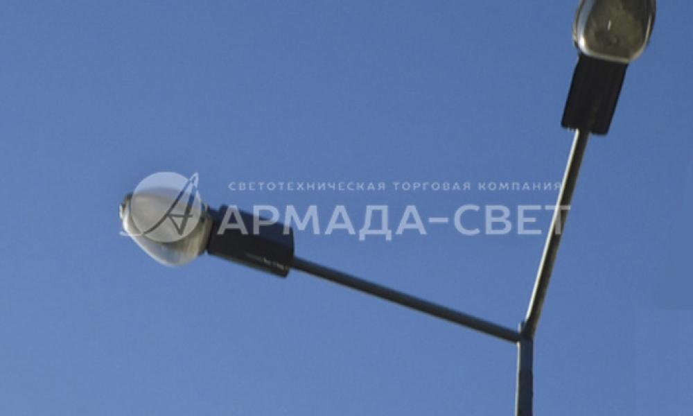 На фото изображен кронштейн под консольные светильники, на котором установлены приборы освещения с газоразрядными лампами. Угол между двумя рожками кронштейна составляет 90 градусов. Конструкция оцинкована для защиты от коррозии, поверх слоя цинка кронштейн окрашен порошковой краской.