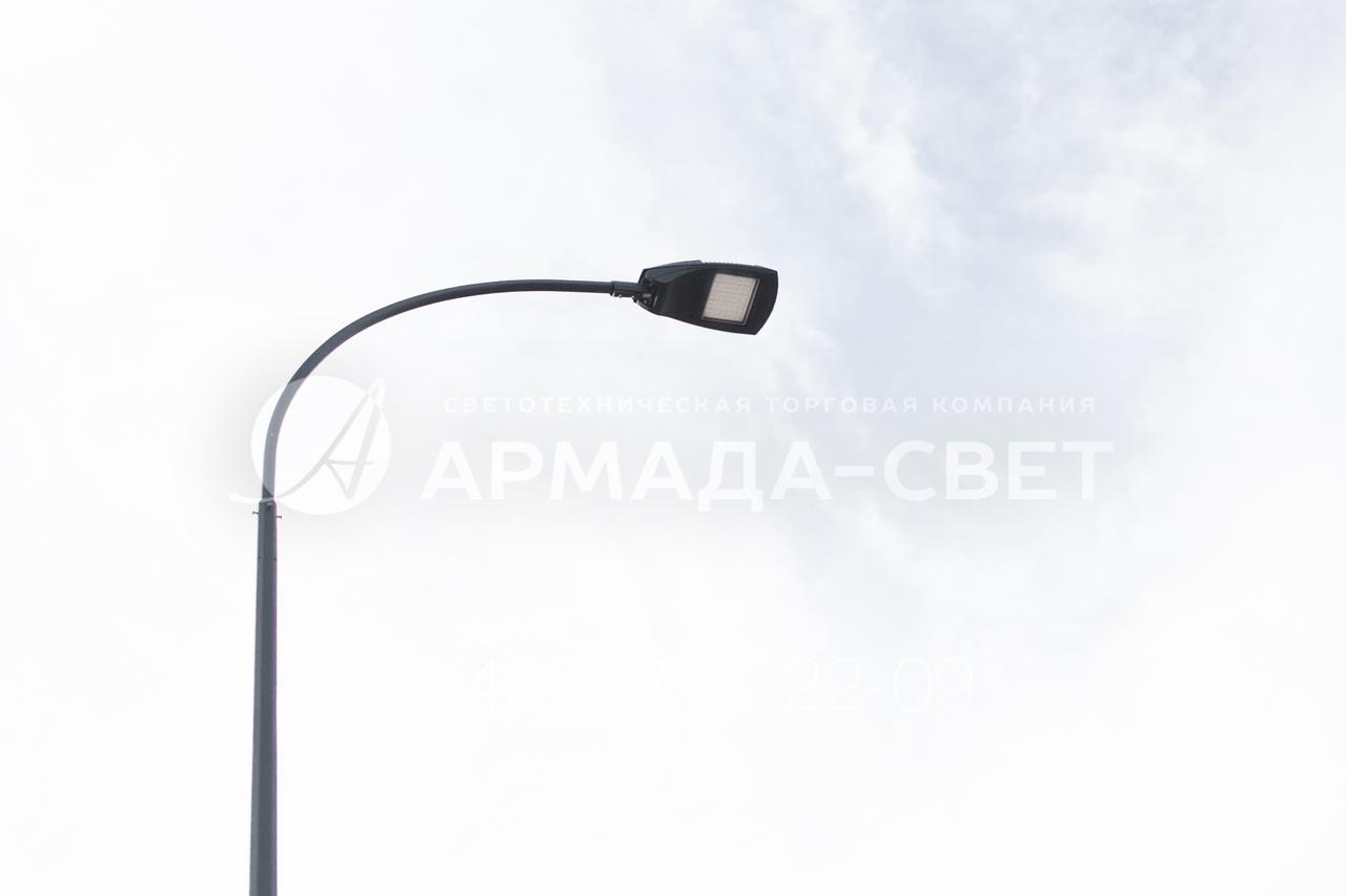 Изображенный на фотографии кронштейн удерживает светодиодный консольный светильник. Он установлен в оголовок граненой конической опоры. Все изделия, включая корпус светильника, окрашены в черный цвет. Он придает конструкции красивый внешний вид, но защита от коррозии выполнена методом горячего цинкования.